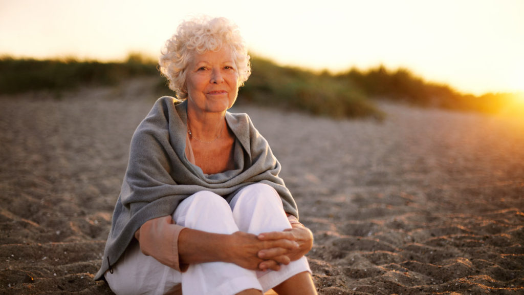 Portrait of happy old woman sitting on the beach. Retired caucasian lady relaxing outdoors
